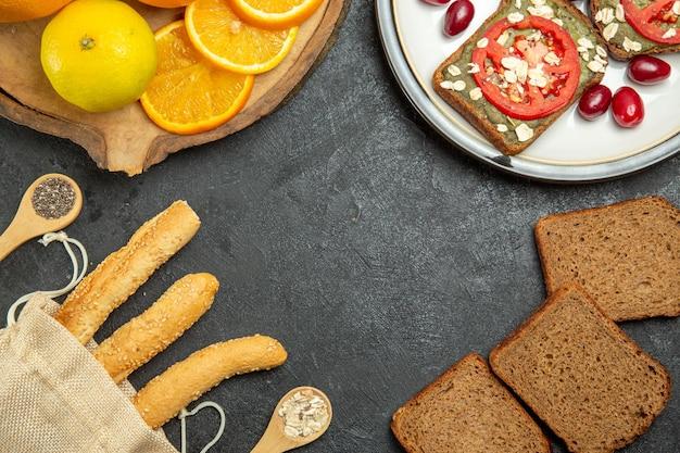 회색 표면에 오렌지와 함께 맛있는 아보카도 샌드위치의 상위 뷰