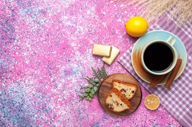 Вид сверху на вкусный торт, нарезанный чашкой чая с корицей и лимонами на светло-розовой поверхности