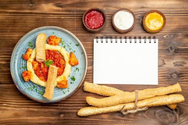 茶色のテーブルにマッシュポテトとパンを添えたおいしいチキンスライスの上面図。皿唐辛子肉骨粉夕食