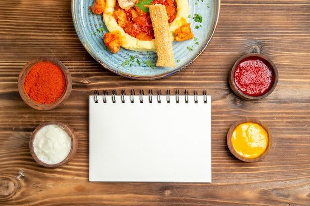 갈색 테이블에 mushed 감자와 조미료와 함께 맛있는 치킨 조각의 상위 뷰.