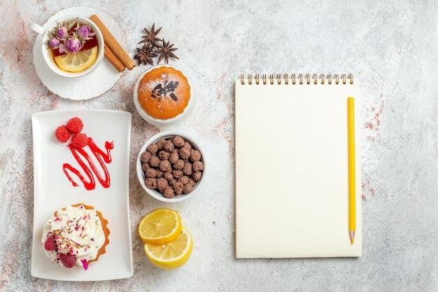 白のお茶とレモンのスライスとおいしいクリーミーなケーキの上面図