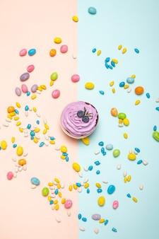 桃と青の背景にカラフルなお菓子の中に置かれたクリームとブルーベリーのおいしいカップケーキの上面図