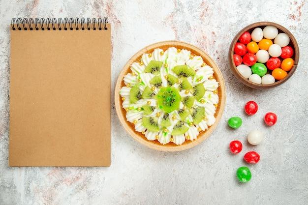 おいしいデザートの上面図は、白いクリームと白いテーブルの上にキャンディーとスライスしたキウイで構成されています