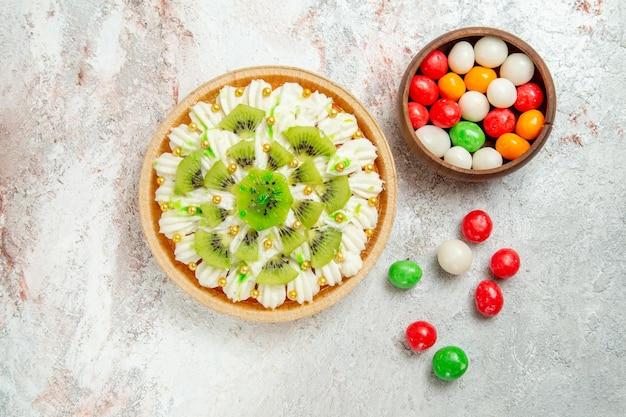 白いテーブルの上においしい白いクリームとスライスしたキウイで作られたおいしいデザートの上面図