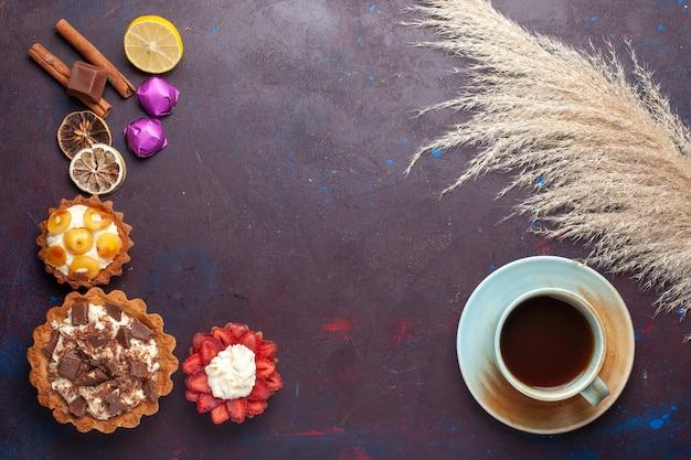 Вид сверху вкусных маленьких пирожных со сливками вместе с конфетами и чаем на темной поверхности