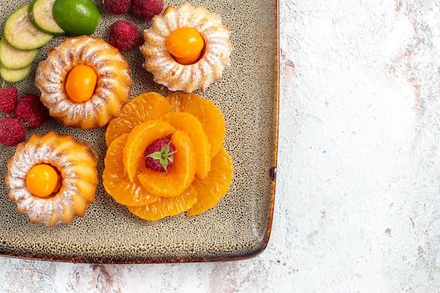 흰색에 얇게 썬 과일과 함께 맛있는 작은 케이크의 상위 뷰