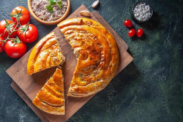 Вид сверху вкусного мясного пирога с красными помидорами на темной поверхности
