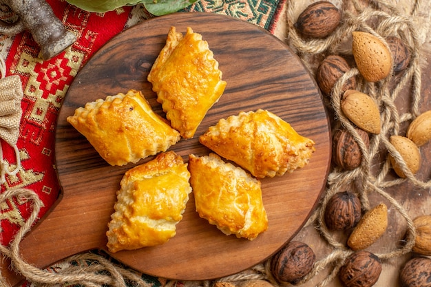 Вид сверху на вкусную ореховую выпечку со свежими грецкими орехами на коричневом столе