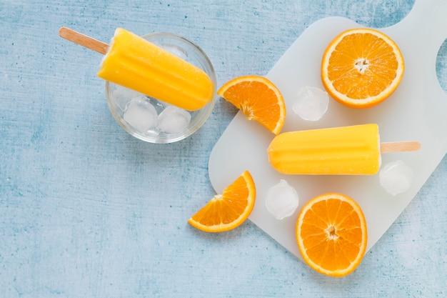 Вид сверху на вкусное фруктовое мороженое со льдом и апельсином