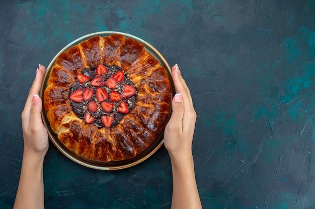 Вид сверху вкусного клубничного пирога на темно-синей поверхности