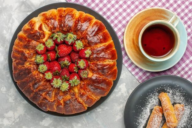 新鮮な赤いイチゴと白い机の上のお茶とおいしいストロベリーパイの上面図