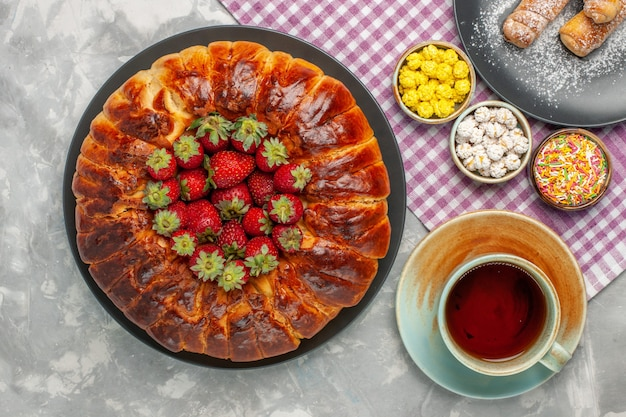 新鮮な赤いイチゴと白い表面にお茶のカップとおいしいストロベリーパイの上面図