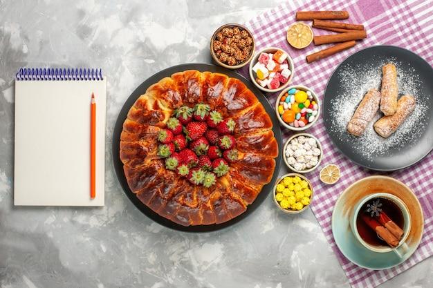 新鮮な赤いイチゴキャンディーと白い表面にお茶のカップとおいしいストロベリーパイの上面図