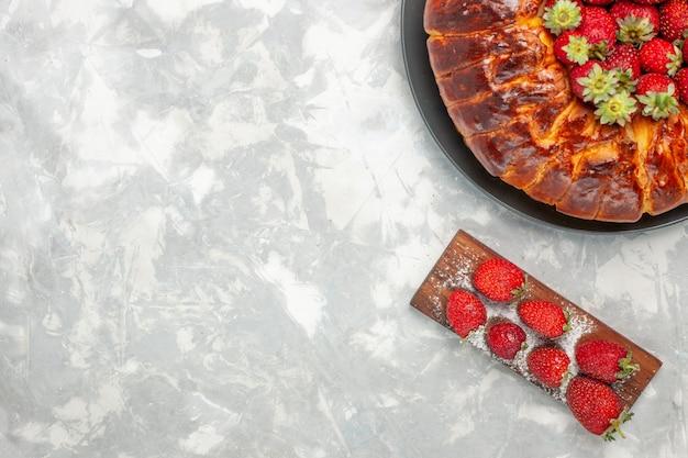 흰색 책상에 신선한 빨간 딸기와 맛있는 딸기 파이의 상위 뷰