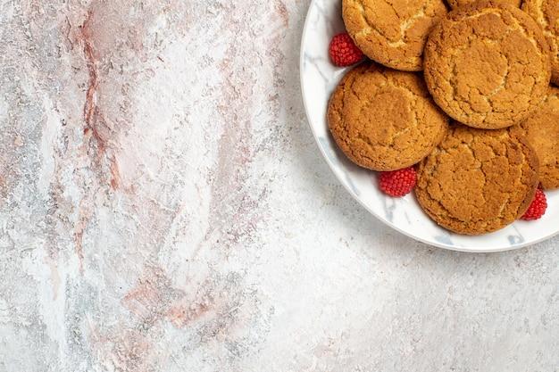 明るい白い表面のプレート内のおいしいシュガークッキーの上面図
