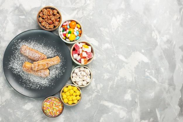 Вид сверху вкусных сладких рогаликов, сахарной пудры с различными конфетами на белой поверхности
