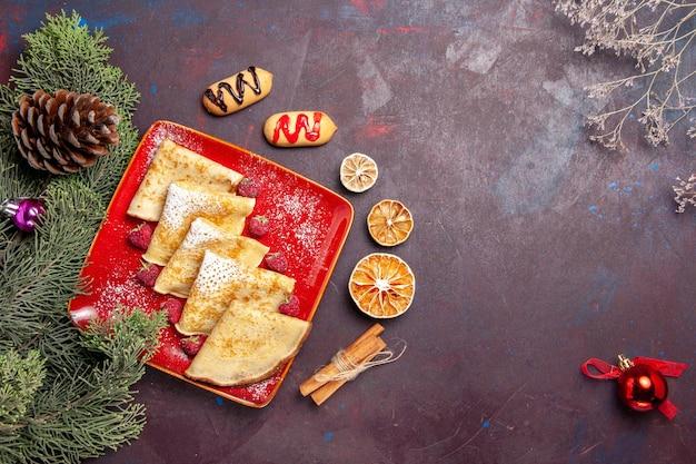 黒いテーブルの上のラズベリーとおいしい甘いパンケーキの上面図