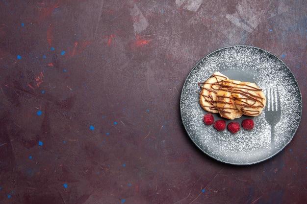 黒いテーブルの上のプレートの内側のお茶のためのおいしい甘いロールスライスケーキの上面図