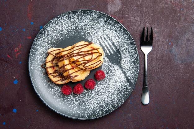 맛있는 달콤한 롤의 상위 뷰는 블랙 접시 안에 차 케이크를 슬라이스