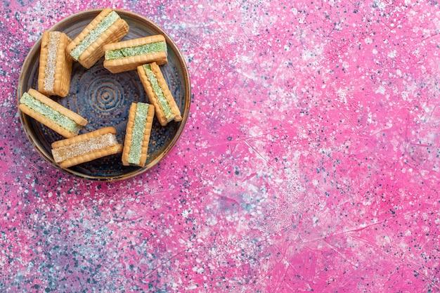 ピンクの表面のプレート内のおいしいワッフルクッキーの上面図