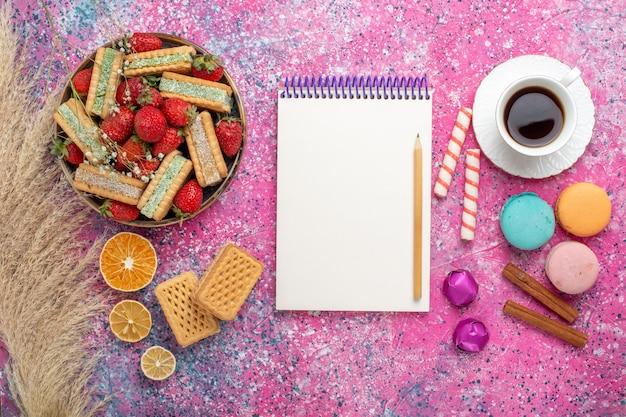 Вид сверху вкусного вафельного печенья с французскими макаронами и свежей красной клубникой на розовой поверхности