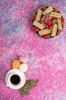 Вид сверху вкусного вафельного печенья со свежей красной клубникой и чаем на розовой поверхности