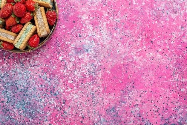 Вид сверху вкусного вафельного печенья со свежей красной клубникой на розовой поверхности