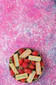 ピンクの表面に新鮮な赤いイチゴとおいしいワッフルクッキーの上面図