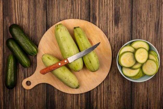 木製の表面に分離されたキュウリとナイフで木製のキッチンボードに分離されたズッキーニの上面図