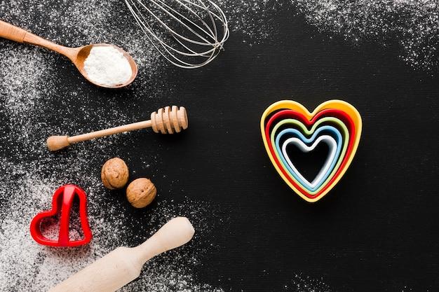 Вид сверху цветных сердечных форм с кухонной утварью и мукой