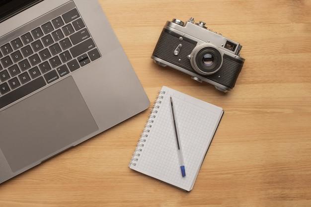Вид сверху на офисный стол для фотосъемки с ноутбуком, блокнотом, камерой и ручкой