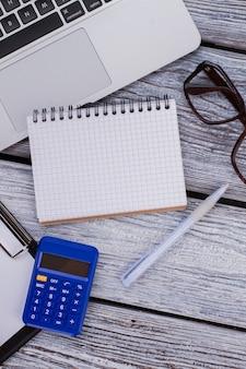 Офисные и финансовые аксессуары и блокнот для копирования пространства. вид сверху. белый деревянный стол.