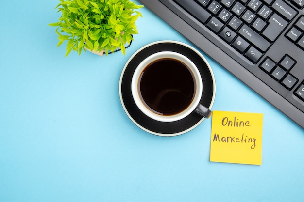 Top view of office concept with a cup of black tea and online marketing writing flower on blue background