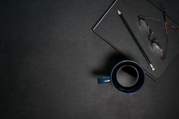 Top view office dark desk table workplace with coffee and supplies.