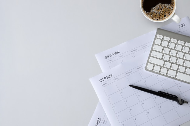 Top view of office desk with coffee cup, keyboard and work schedule on white table