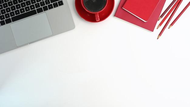 Офисный стол вид сверху с портативным компьютером, красной чашкой кофе, красной записной книжкой и карандашом на белом столе.