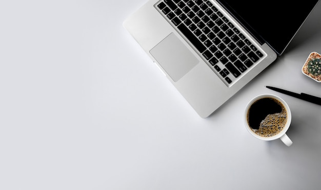 Top view of office desk workspace with coffee cup, keyboard and work schedule on white table