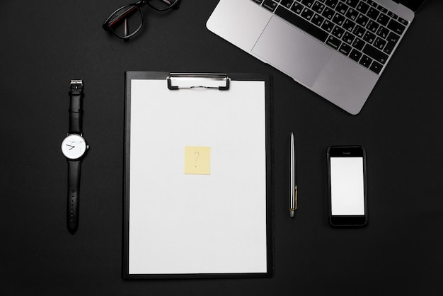 Top view office desktop with white sheet of paper with free copy space and yellow paper for notes with a question mark. blank phone, laptop and supplies background.