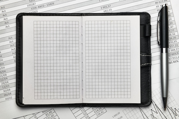 Top view of office employee's desk - empty notepad with blank pages and financial reports, analysis and accounting