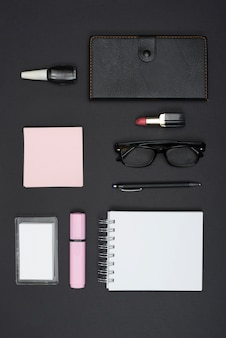 Top view of office stationery and lipstick; nail varnish over black background