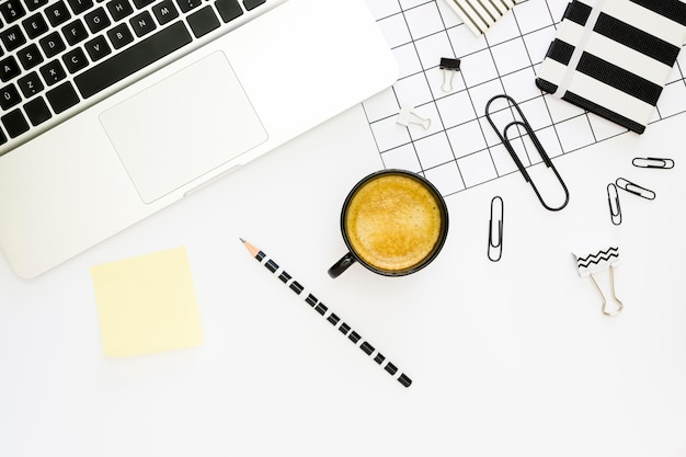 Top view of office stationery with coffee and laptop