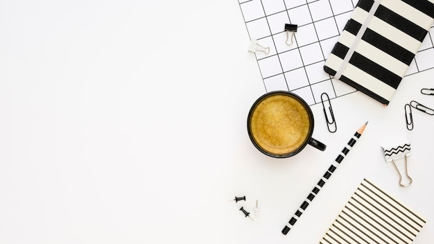 Vista dall'alto di cancelleria per ufficio con caffè e graffette
