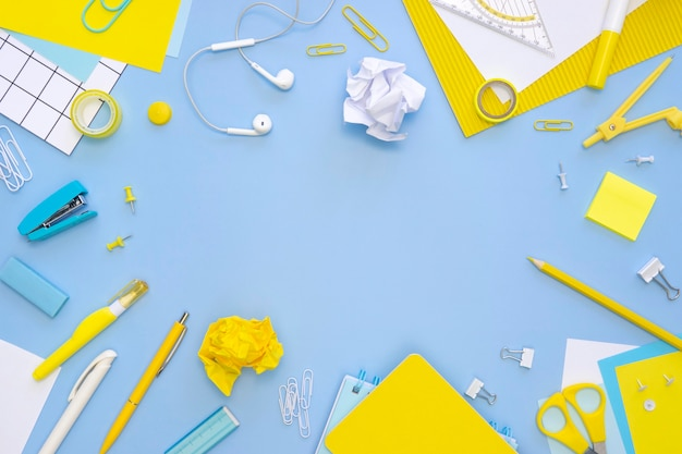 Top view of office stationery with earphones and stapler