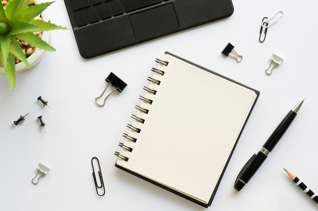 Top view of office stationery with notebook and laptop