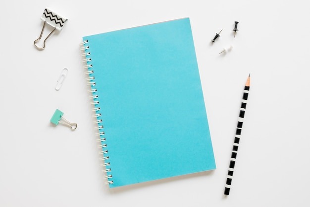 Top view of office stationery with notebook and paper clips