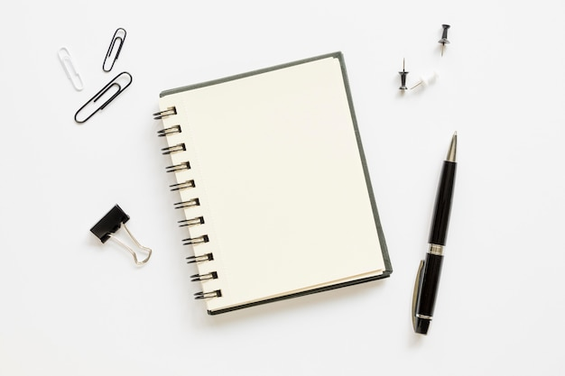 Top view of office stationery with notebook and paper pins