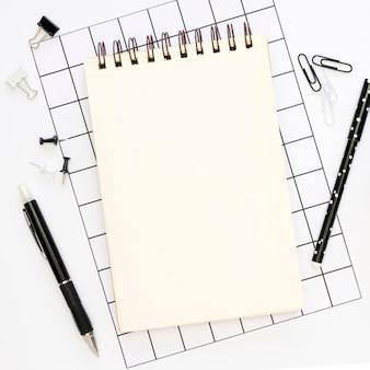 Top view of office stationery with notebook and pens