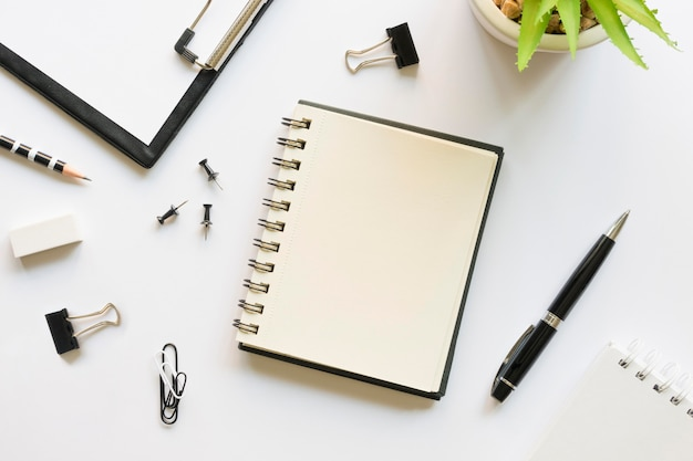 Top view of office stationery with notebook and pins