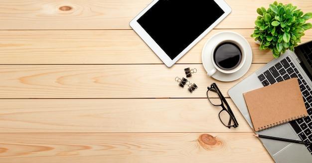 Стол офисный стол вид сверху. рабочее пространство с пробелом, канцелярскими товарами, ноутбуком, карандашом, зелеными листьями и кофейной чашкой на деревянном фоне.