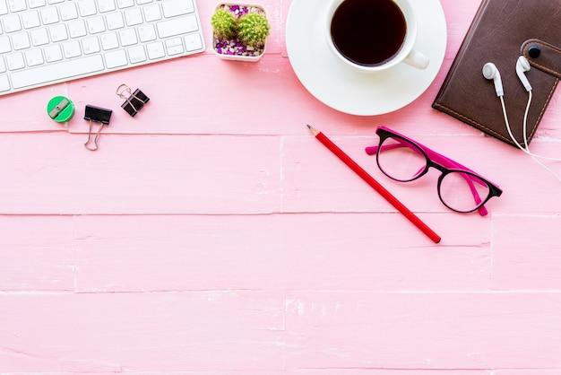 トップビューピンクの木製の背景にオフィステーブル。